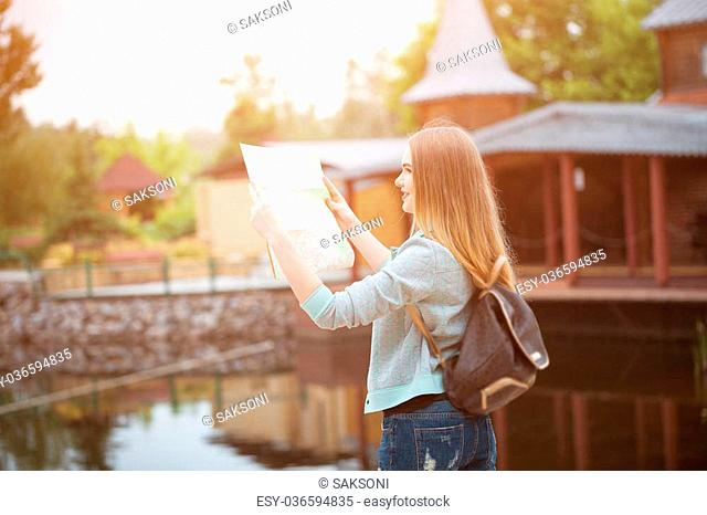 Traveler girl searching right direction on map, orange sunset light, traveling along Europe, freedom and active lifestyle concept