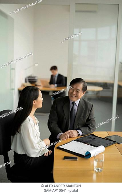 Singapore, Businesswoman having discussion with senior colleague in office