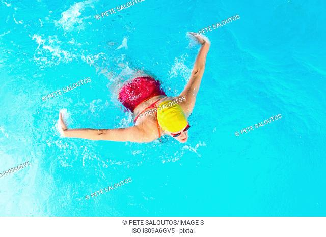 Mature woman doing butterfly stroke in swimming pool