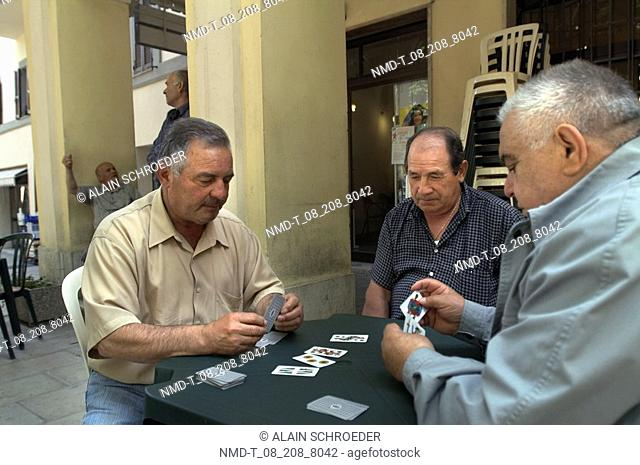 Three mature men playing cards on the terrace of a bar, Nocera Umbra, Umbria, Italy