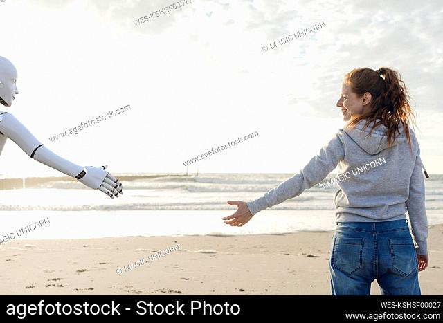 Smiling woman standing on the beach reaching for robot hand