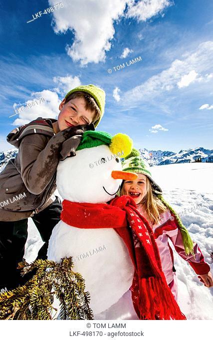 Two children posing with a snowman, Planai, Schladming, Styria, Austria