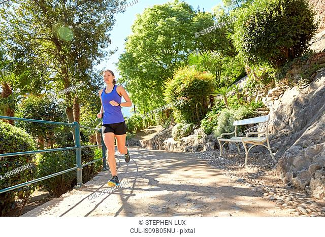 Young woman running along rural pathway, Meran, South Tyrol, Italy