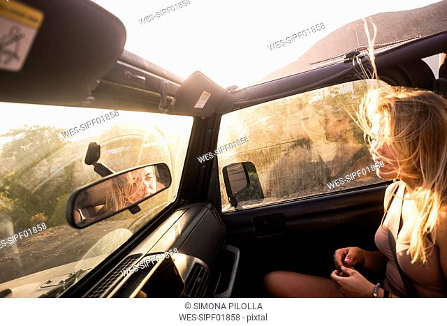 Blond woman with blowing hair sitting in car at sunset
