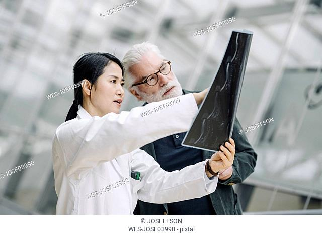 Female doctor discussing x-ray with senior patient