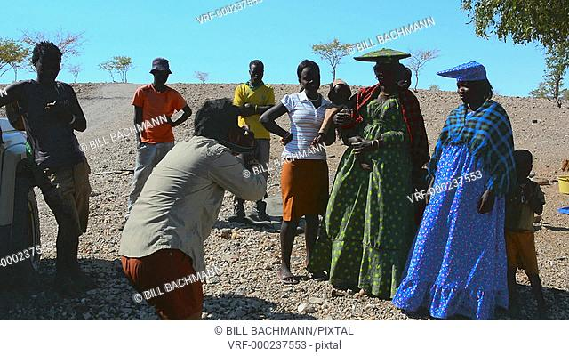 Namibia Africa Northern Desert tourists relating with colorful Herero tribe women in plaid dress and hat and traditional costume in Tomakas in Puros Conservancy...