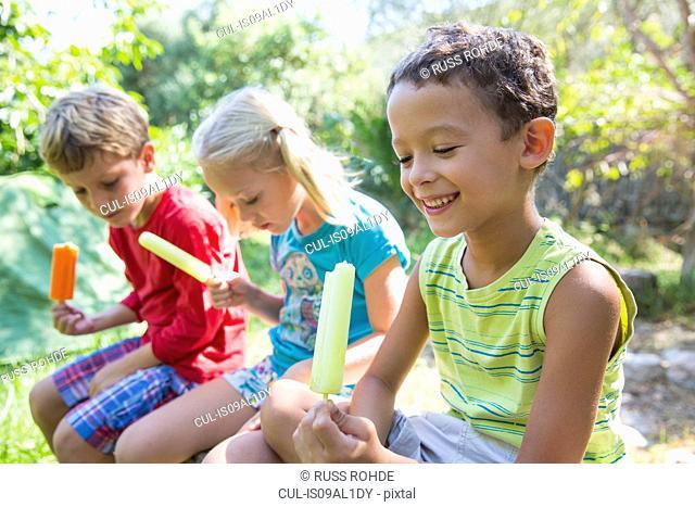 Three children in garden eating ice lollies