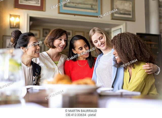 Smiling women dining and talking in restaurant