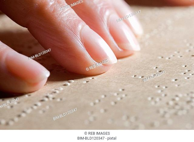 Close up of Hispanic woman reading Braille