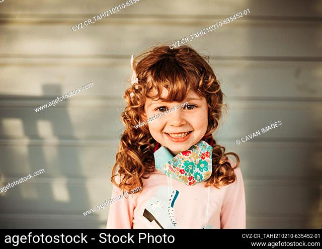 Portrait of young girl smiling wearing handmade face covering outside