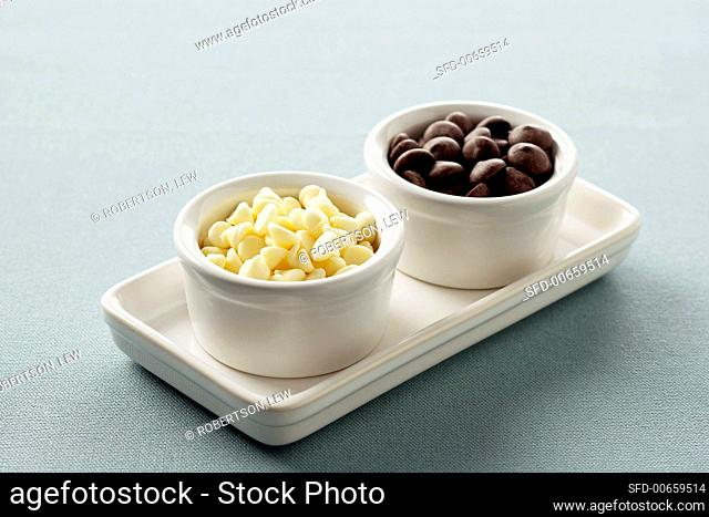 Two Small White Bowls on a Tray, One with White Chocolate Chips and One With Milk Chocolate Chips