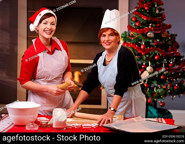 Mother and daughter baking christmas cake together, looking at camera, smiling