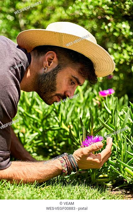 Man looking at a flower in garden
