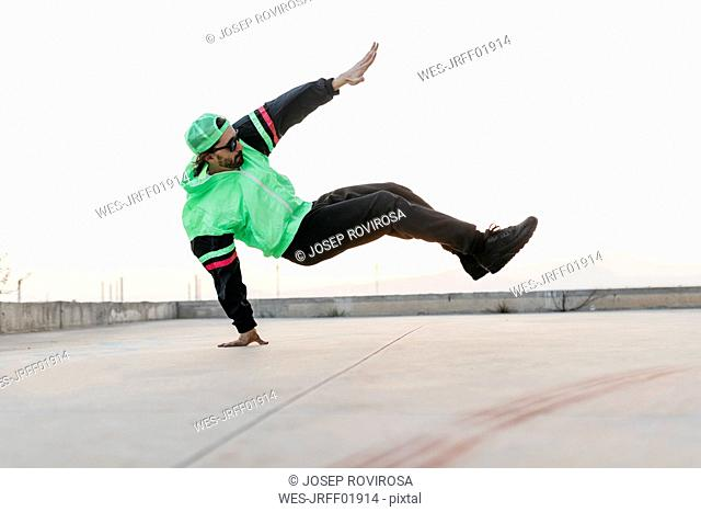 Man doing breakdance in urban concrete building, standing on hand