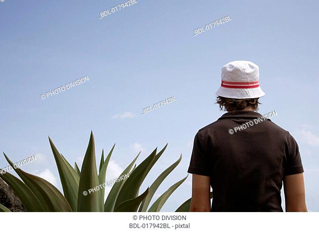 rear view of young woman with hat standing beside cactus