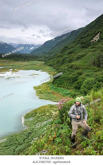 Swiss biologist and photographer glassing while standing on a cliff overlooking Katmai Coast, Kukak Bay, Southwest Alaska