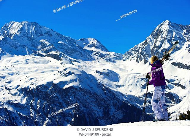 A skier looks out over a stunning winter snowy mountains