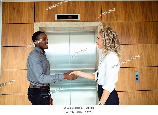 Business executives shaking hands near lift
