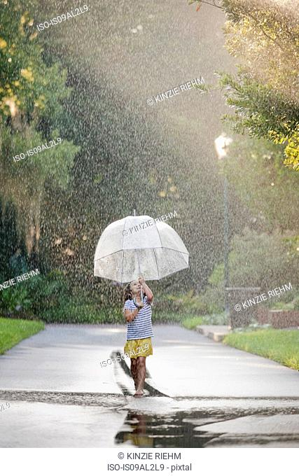 Barefoot girl holding up umbrella and walking through puddles on street