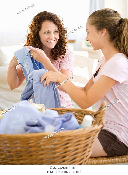 Hispanic mother and daughter folding laundry together