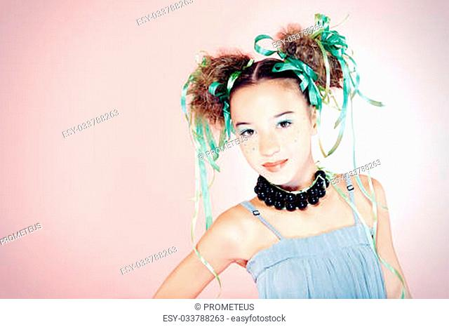 Portrait of a happy funny girl with holiday make-up, hairstyle and dress