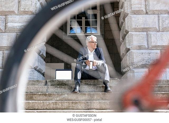 Senior businessman with bicycle sitting on stairs outdoors with laptop and travel mug
