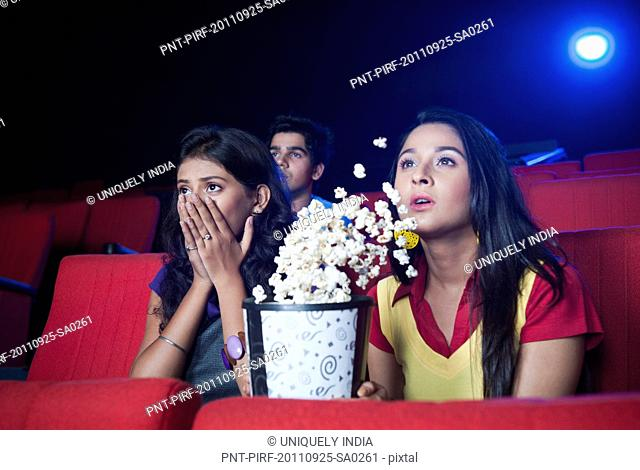 Two female friends looking surprised while watching movie in a cinema hall