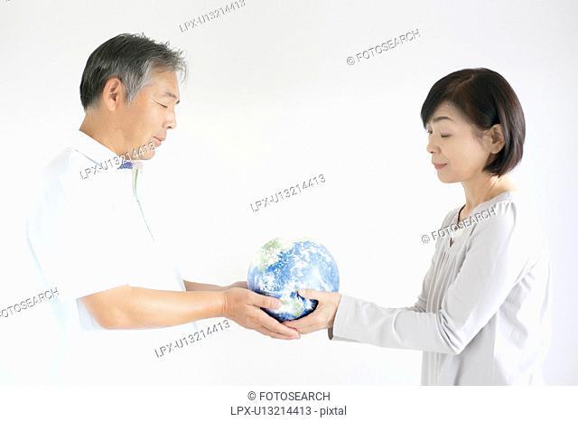 Mature Couple Holding Globe