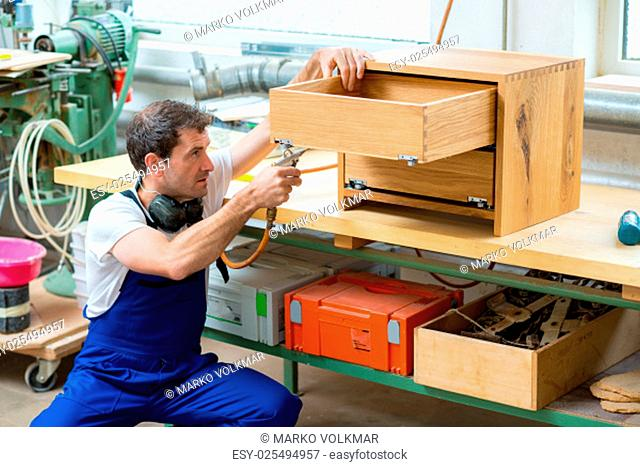 worker in a carpenter's workshop using drilling machine