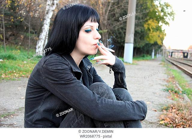 Girl sit and smoke near rails