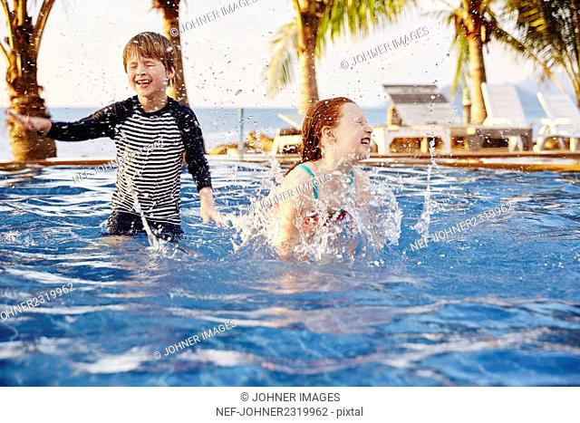 Happy boy and girl in swimming-pool
