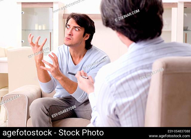 Young male patient discussing with psychologist personal problems