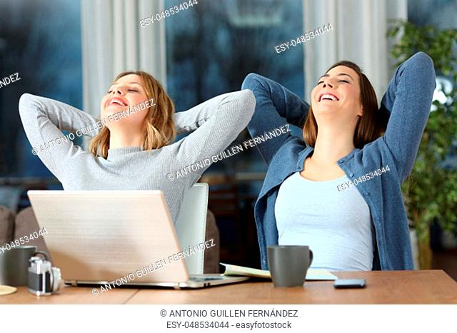 Two satisfied tourist women relaxing sitting on chairs at apartment on vacations in the evening