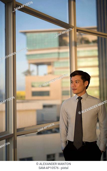 Singapore, Businessman standing at window in office