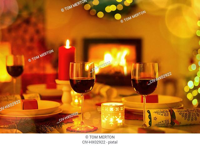 Red wine and candles on ambient Christmas table in front of fireplace
