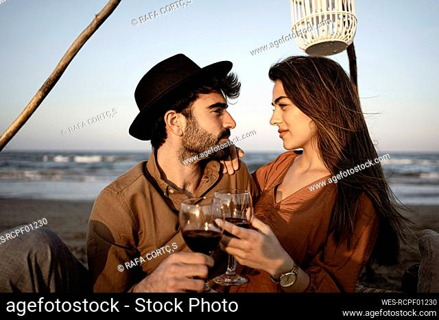 Couple looking at each other while holding drinks during picnic