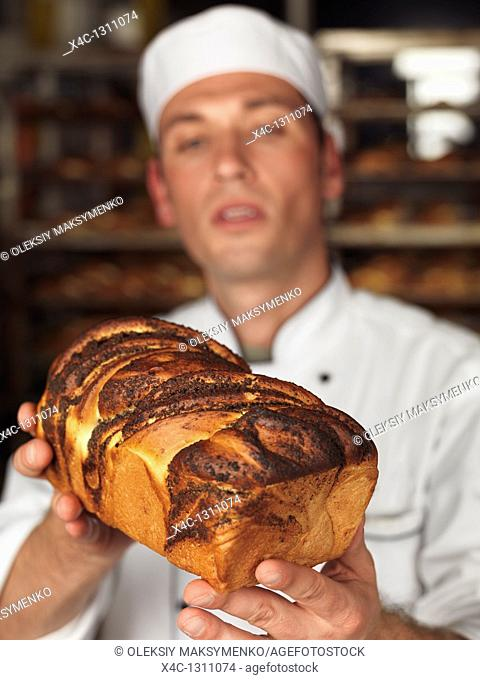 Baker looking at a freshly baked loaf of sweet bread in his hands  Focus is on the bread