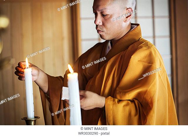 Side view of Buddhist monk with shaved head wearing golden robe kneeling indoors in a temple, lighting white candle