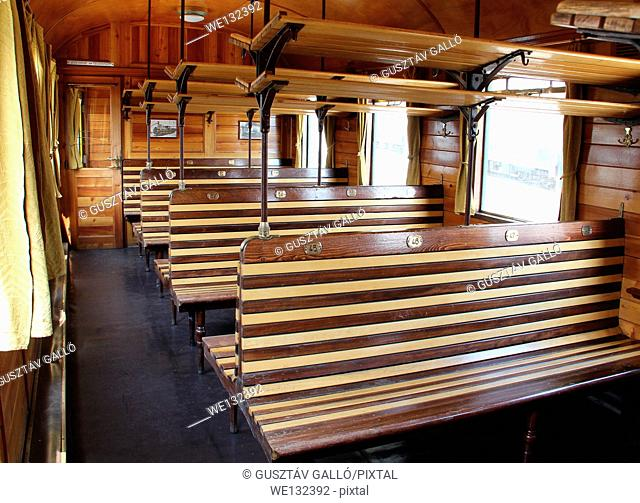 Old empty wooden benches inside the railway carriage