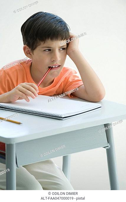 Elementary school student sitting at desk, leaning on elbow, chewing end of pencil