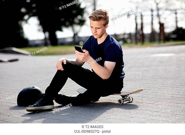 Teenage skateboarder texting