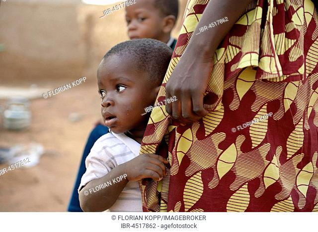 Boy, 15 months, leaning on mother, village of Toeghin, Oubritenga province, Plateau Central region, Burkina Faso