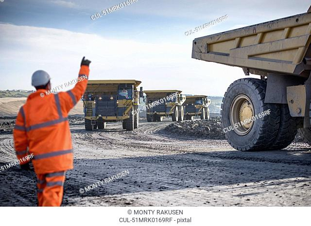 Worker directing trucks at surface mine