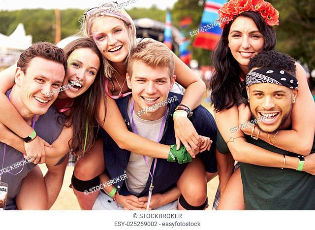 Friends giving piggy backs at a music festival