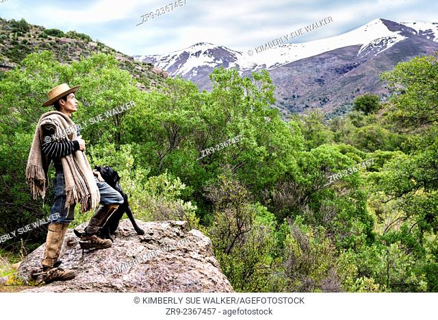 Chilean cowboy (arriero) stands on a rock and looks out over the Andean mountain with his black dog beside him in the valley in El Toyo region of Cajon del...