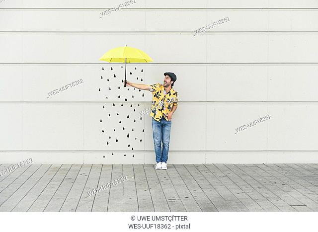 Digital composite of young man holding an umbrella at a wall with raindrops
