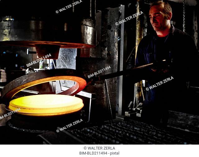 Caucasian worker melting steel in factory