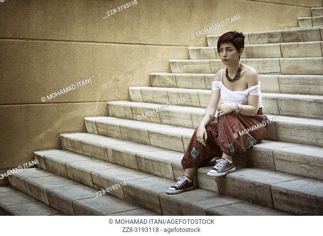 Beautiful young woman sat on the steps outdoors looking away