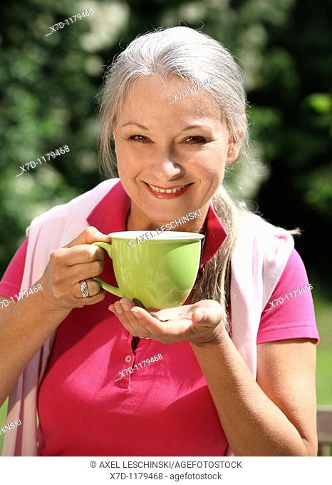 older woman relaxing in garden drinking a cup of coffee