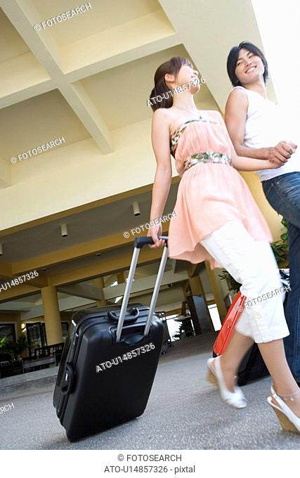 Young couple carrying suitcases, Saipan, USA